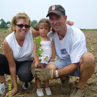 New Vines BB Owners planting a grapevine with a young girl who is there granddaughter